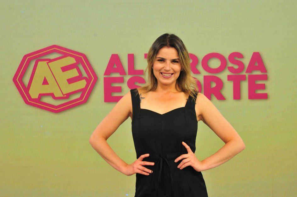 Isabel Guimarães, apresentadora, posa em frente ao telão com a marca do Alterosa Esporte ao fundo