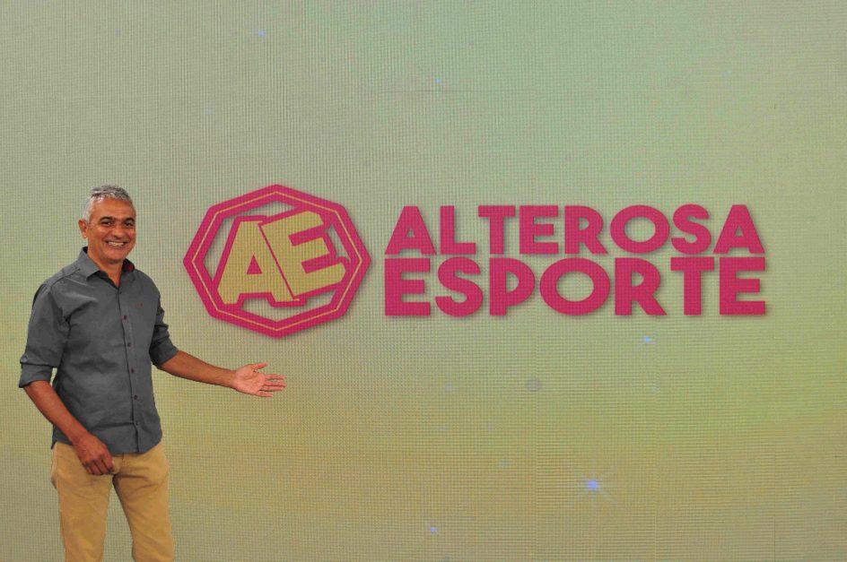 Leopoldo Siqueira, apresentador do Alterosa Esporte, posa em frente a um telão de led que exibe a marca do programa